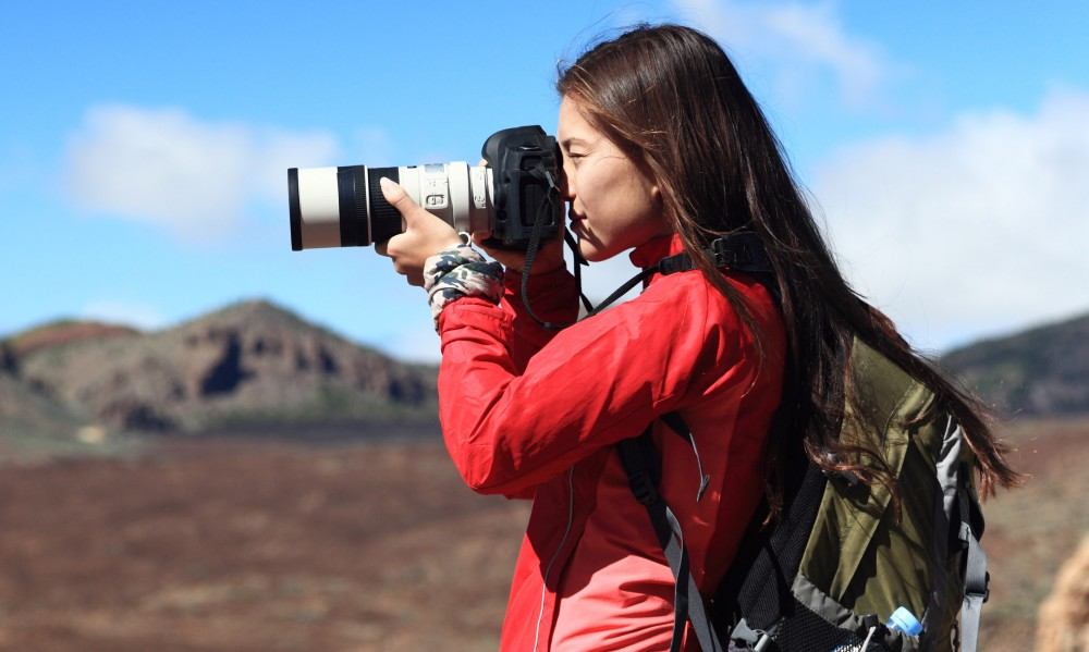 Woman with backpack using a dSLR camera and zoom lens