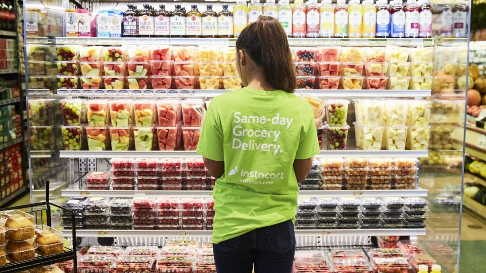 An Instacart Shopper looking at selections of fruit.