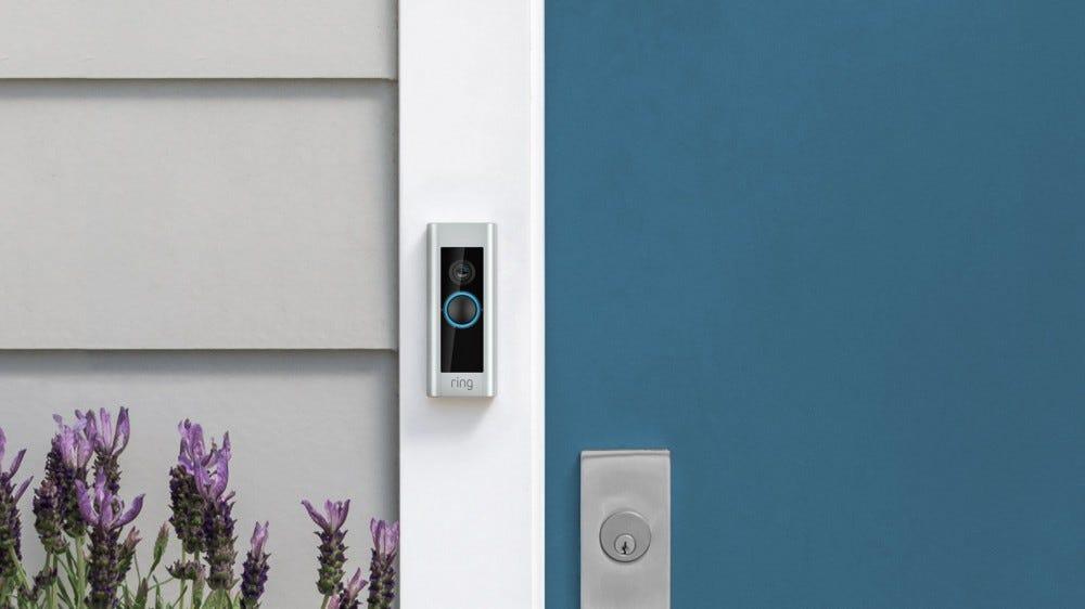 A Ring Video Doorbell Pro next to a blue door.