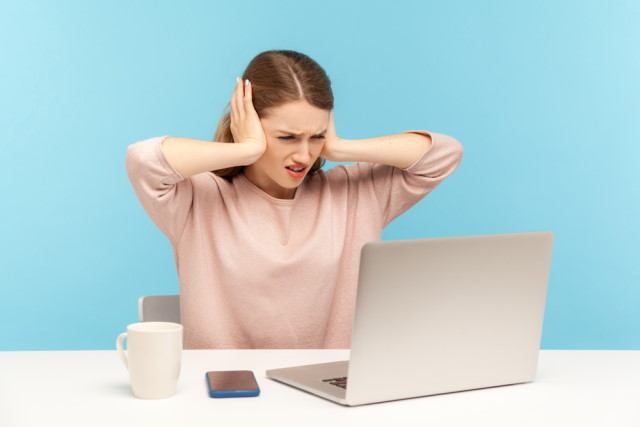 Woman at laptop covering ears