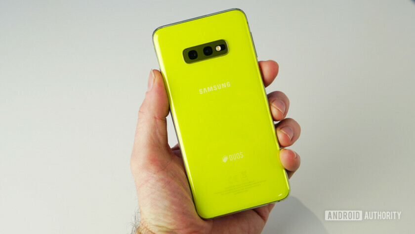 A hand holding the Samsung Galaxy S10e showing the back view.