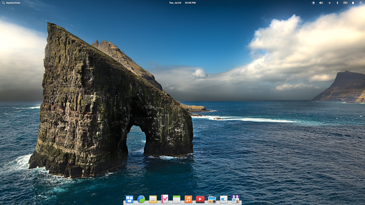 elementary OS 6 desktop with wallpaper featuring a horseshoe shaped rock in the sea.