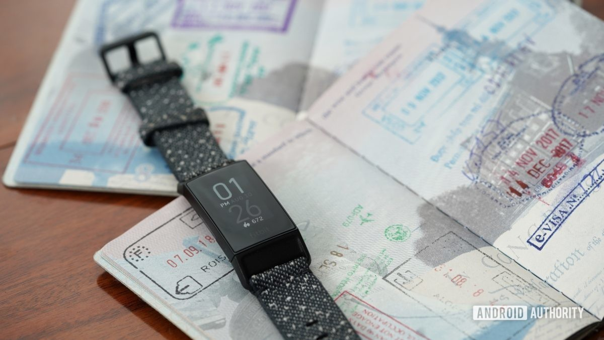 A Fitbit Charge 4 rests on open passports alluding to the ability to change the time on your Fitbit based on time zones.