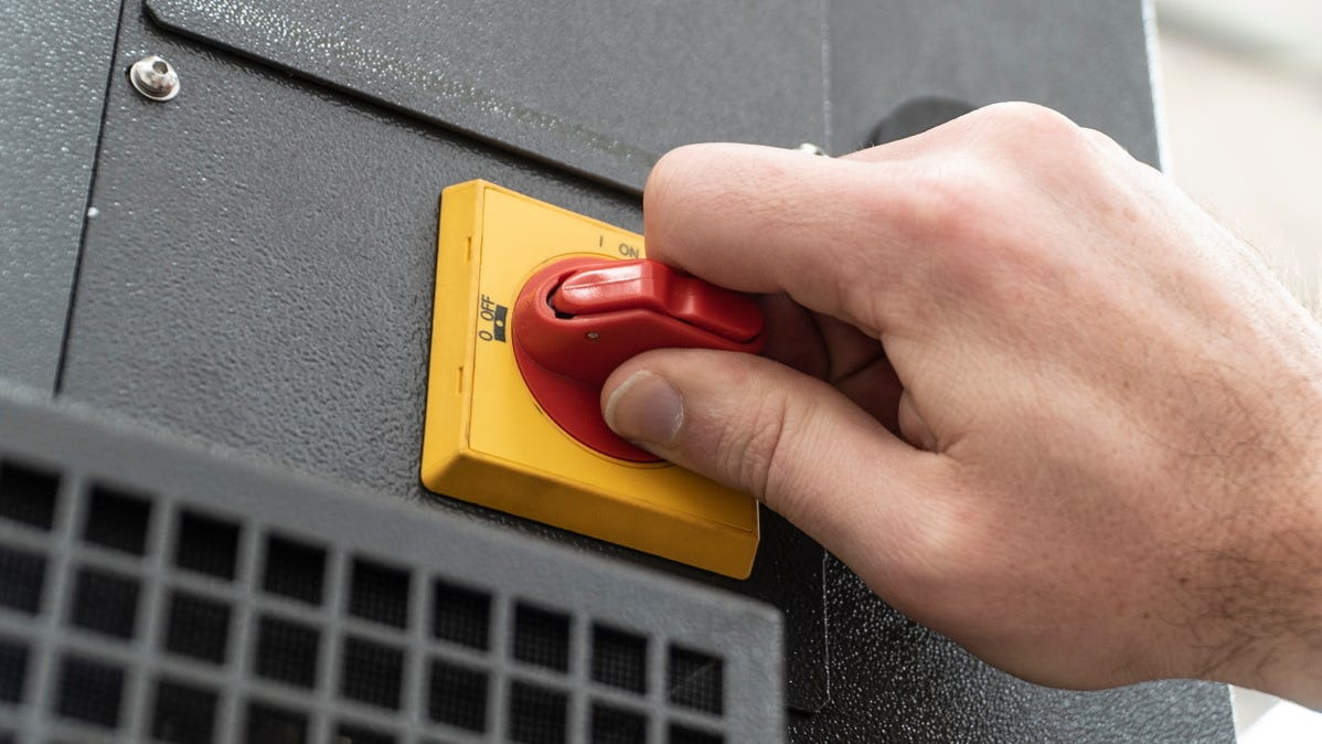 A red emergency stop switch on an industrial machine.