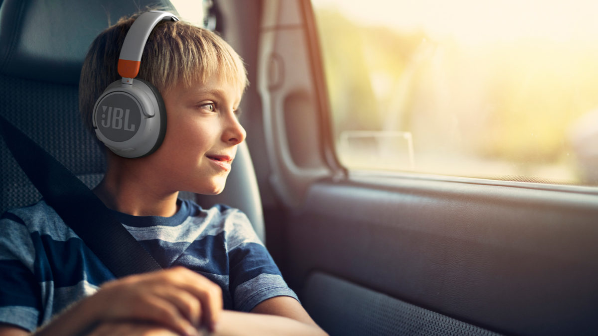 A young blonde child sits in a car while wearing the JBL JR460NC headphones in gray.